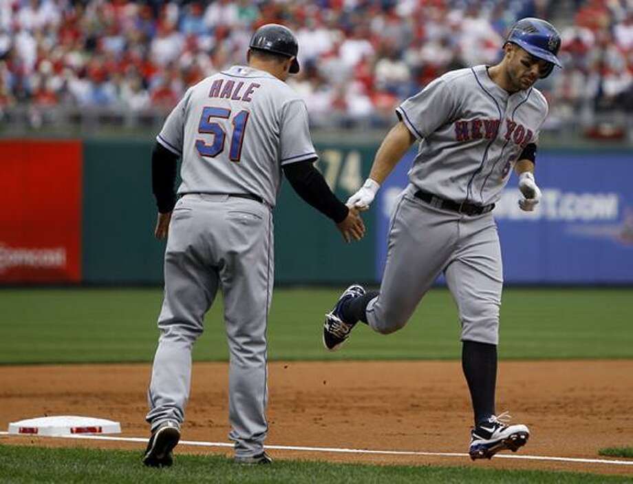 New York Mets' David Wright, right, celebrates with third base coach Chip Hale after Wright's home run off Philadelphia Phillies pitcher Cole Hamels, not pictured, in the second inning of a baseball game, Sunday in Philadelphia. (AP Photo/Matt Slocum) Photo: AP / AP