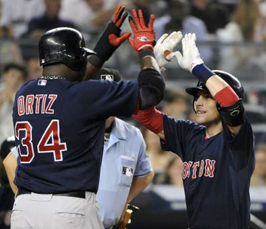 Boston Red Sox Jed Lowrie, right, high-fives with David Ortiz after Lowrie hit a three-run home run during the second inning of a baseball game against the New York Yankees Friday, Sept. 24, 2010 at Yankee Stadium in New York. (AP) Photo: AP / FR51951 AP
