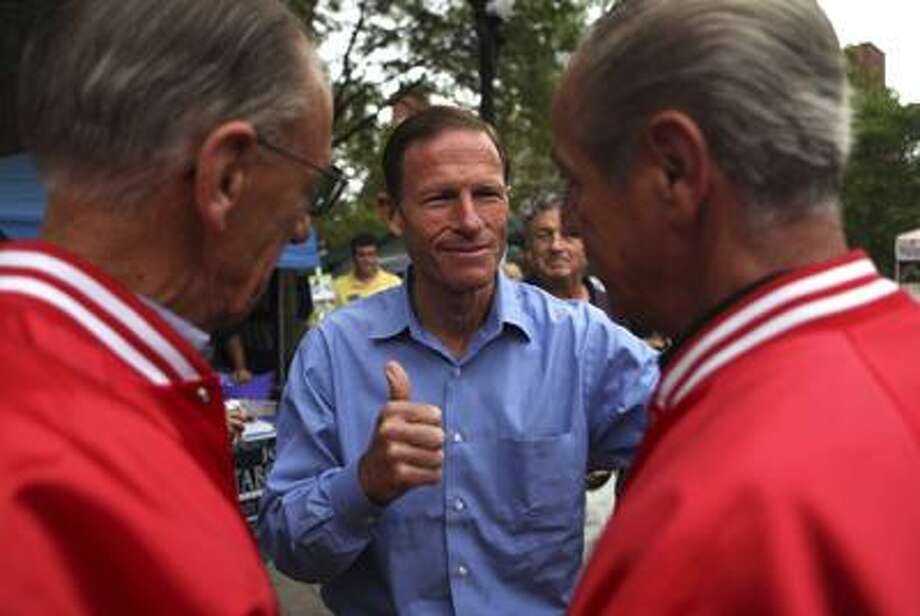"""Democratic candidate for U.S. Senate, Richard Blumenthal, speaks with retired Marines John Hill and Larry Miguel during a campaign stop at """"The Taste of Danbury"""" in Danbury on Sunday, Sept. 12. (AP) Photo: AP / AP"""