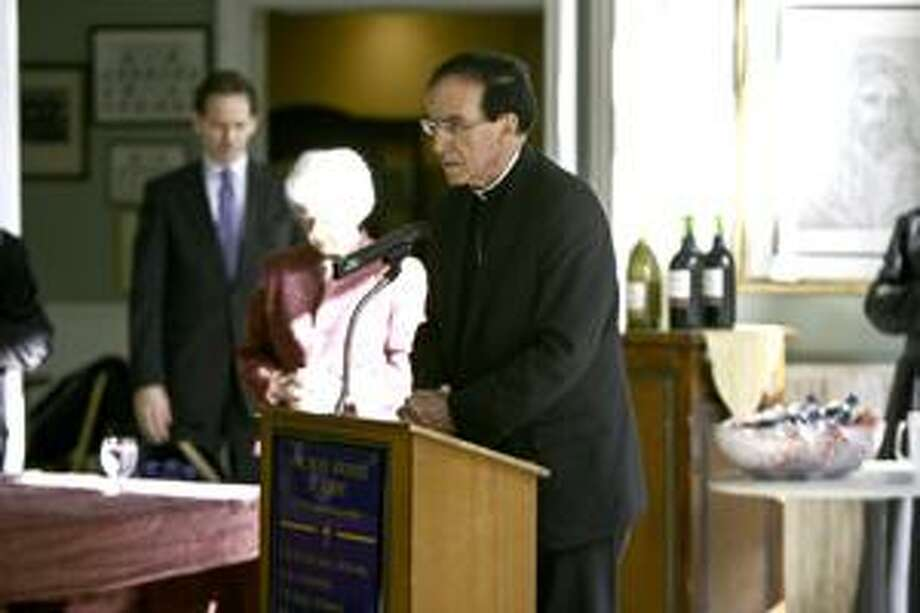 Patrick Holland The Most Rev. Henry J. Mansell, archbishop of Hartord, prays during the redication of the I-libary in the name of Pope John Paul II the libary offers information on Bioethics.
