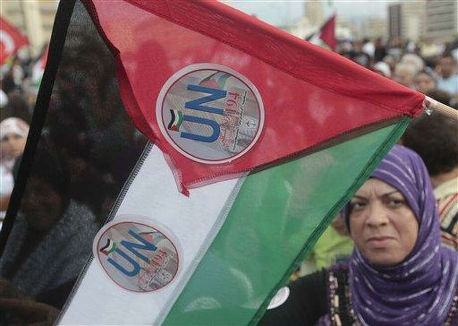 A Palestinian woman waves a Palestinian flag with a UN stickers attached on it, during a rally in support of the Palestinian bid for statehood recognition in the United Nations, at a Palestinian refugee camp, in Beirut, Lebanon, Friday Sept. 23, 2011. Defying U.S. and Israeli opposition, Palestinians were determined to ask the United Nations on Friday to accept them as a member state, sidestepping nearly two decades of troubled negotiations in the hope this dramatic move on the world stage would reenergize their quest for an independent homeland. (AP Photo/Hussein Malla) Photo: AP / AP