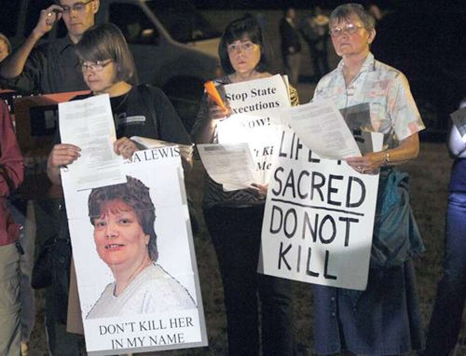 Death penalty protestors hold signs as they protest the execution of Teresa Lewis outside the Greensville Correctional Center in Jarratt, Va., Thursday, Sept. 23, 2010. Teresa Lewis was executed and pronounced dead at 9:13 p.m. (AP Photo/Steve Helber) Photo: ASSOCIATED PRESS / AP