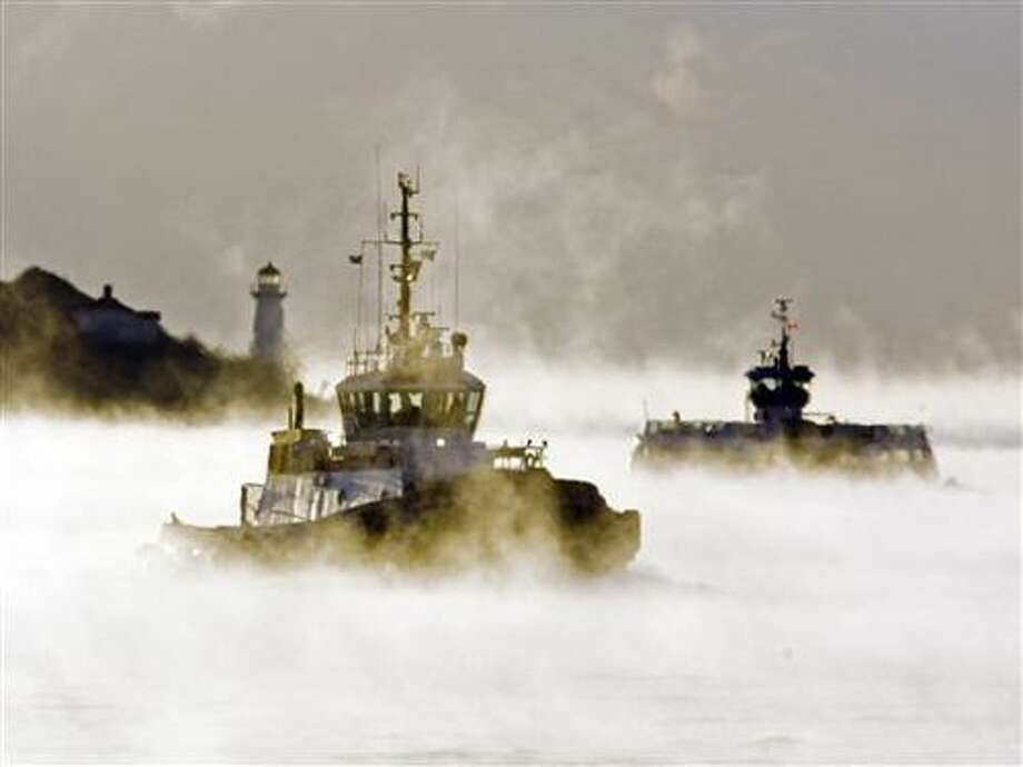 A ferry and tug boat cross the harbour through Arctic sea smoke  in Halifax on Monday, Jan. 24, 2011. The evaporation fog occurs when very cold air drifts across relatively warm water. Wind chill warnings are in effect across much of Eastern and Central Canada.  (AP Photo/The Canadian Press, Andrew Vaughan) Photo: AP / THE CANADIAN PRESS