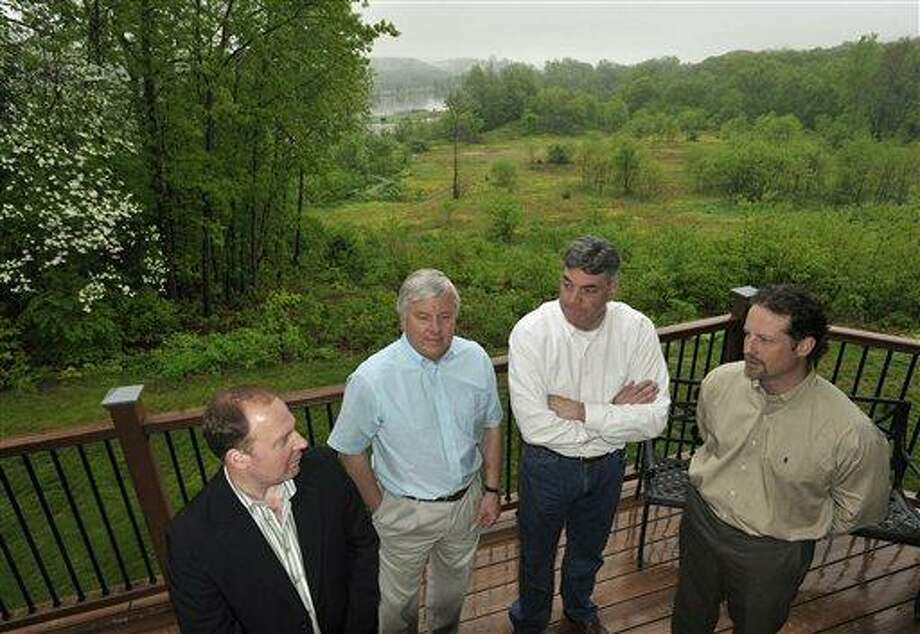 Riverhouse development partners Mark Poole, left, Steve Rocco, second from left, Trevor Furrer, second from right, and Jim Bucko, right, talk to each other as they stand in front of 17 acres of state owned land adjacent to their business in Haddam, Conn., Thursday, May 19, 2011.  A proposal to swap state-owned open space for land adjacent to a state forest is drawing praise for its potential to bring tourism to Haddam. But critics say state conservation land should not be used for private development.  (AP Photo/Jessica Hill) Photo: AP / AP2011
