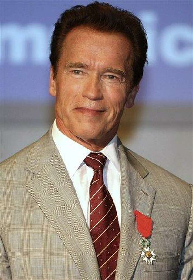 FILE - In this April 4, 2011 file photo, actor and former California Gov. Arnold Schwarzenegger, poses after receiving the insignia of Chevalier in the Order of the Legion of Honor during the MIPTV (International Television Programme Market) in Cannes, southern France. Schwarzenegger delayed his Hollywood comeback Thursday, May 19, 2011 as he braced for what could be a costly divorce prompted by revelations that he had an affair and child with a housekeeper who worked for his family for 20 years. (AP Photo/Lionel Cironneau, File) Photo: ASSOCIATED PRESS / AP2011