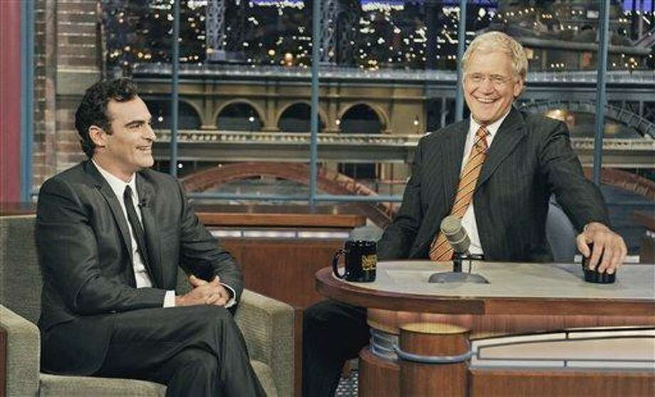 "In this photo released by CBS, actor Joaquin Phoenix, left, joins host David Letterman on the set of the ""Late Show with David Letterman,"" Wednesday, Sept. 22, 2010, in New York. This is Phoenix's first television appearance and first visit to the CBS broadcast since February 2009. (AP Photo/CBS, Jeffrey R. Staab) Photo: AP / CBS"