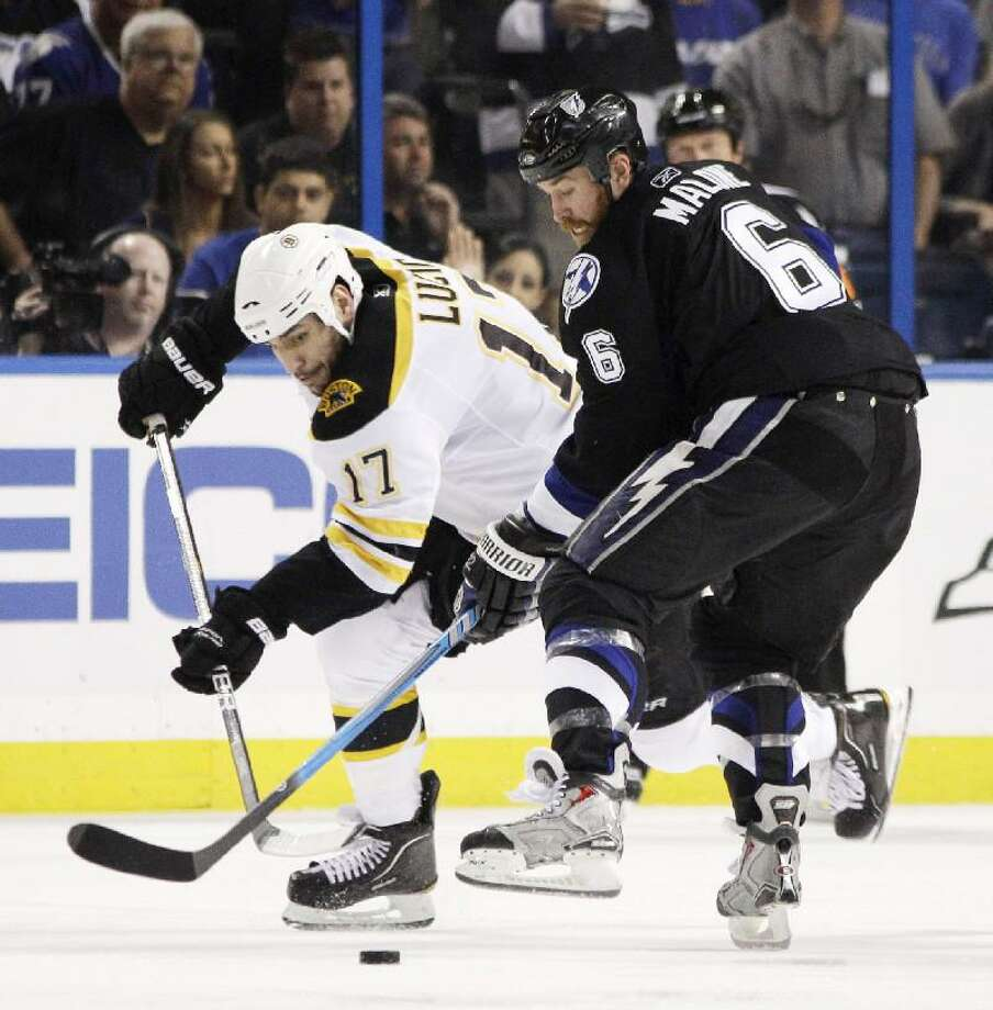 ASSOCIATED PRESS Boston Bruins left wing Milan Lucic (17) and Tampa Bay Lightning left wing Ryan Malone (6) vie for the puck in the second period of Game 4 of the Stanley Cup playoffs Eastern Conference final Saturday in Tampa, Fla.