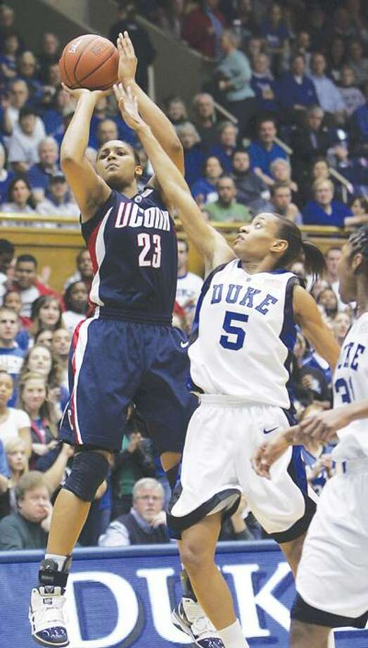 UConn's Maya Moore (23) shoots next to Duke's Jasmine Thomas (5) during the first half of Monday's game. (Associated Press) Photo: AP / The News & Observer