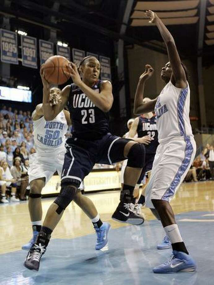 Connecticut forward Maya Moore (23) drives the ball to the basket pass North Carolina guard Italee Lucas (50) and center Waltiea Rolle (32) during the second half of an NCAA college basketball game in Chapel Hill, N.C., Monday, Jan. 17, 2011. Connecticut won 83-57.  (AP Photo/Jim R. Bounds) Photo: ASSOCIATED PRESS / AP2011