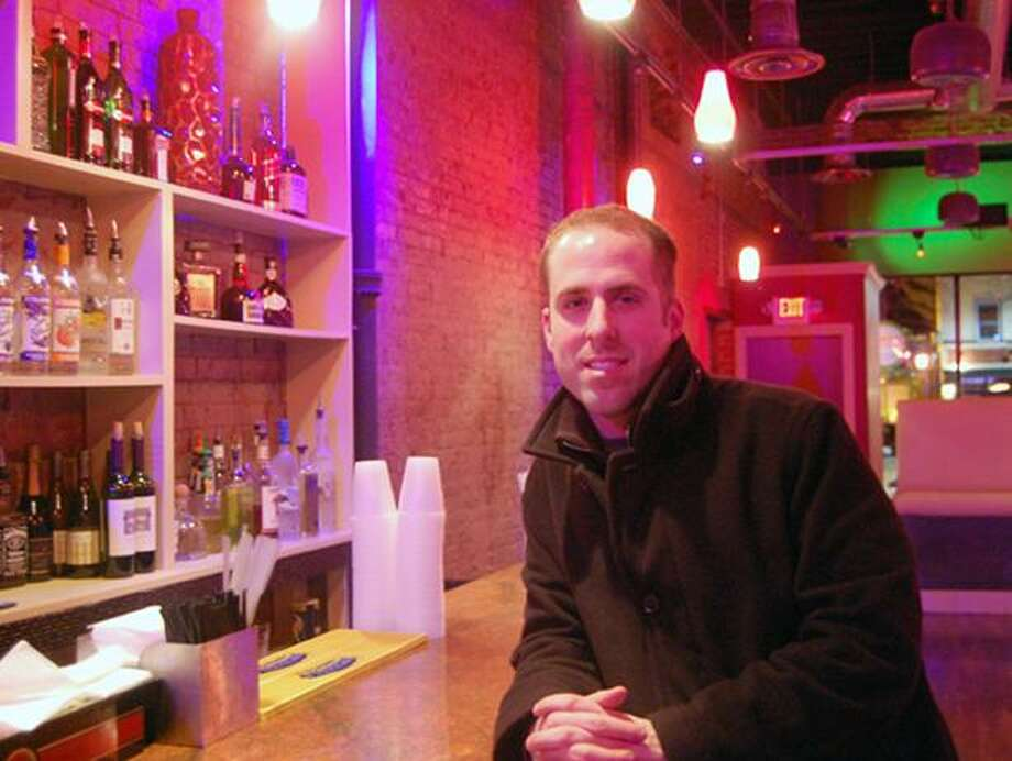 Tyler DeVecchis, owner of Public Bar & Grill, leans on the bar inside Public Friday night.