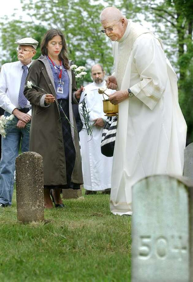 "The Middletown Press) St. Vincent DePaul Place Executive Director Ron Krom reads the name of an individual buried in the cemetery at Conecticut Valley Hospital as Deacon Peter Gill of St. Colman Parish prepares to bless the grave with holy water Wednesday. Donald Pascale, far left, a client at CVH, said, ""I'm glad these deceased souls are getting their names back."" At far right are Mary and Bob Byrnie. Bob's grandfather is buried there."