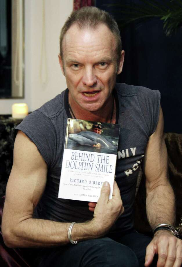 """Sting speaks while showing a book written by Ric O'Barry, former trainer for the 1960s """"Flipper"""" TV series and star of Oscar-winning documentary """"The Cove"""" that depicts the dolphin hunt in the town of Taiji in southwestern Japan, during an interview with The Associated Press when O'Barry visited the British singer before his concert in Tokyo Wednesday. Sting wants to help save dolphins still being brutally slaughtered in Japan, but he believes the best way is by starting a debate, not by forcing foreign opinion. (AP Photo/Koji Sasahara) Photo: ASSOCIATED PRESS / AP2011"""