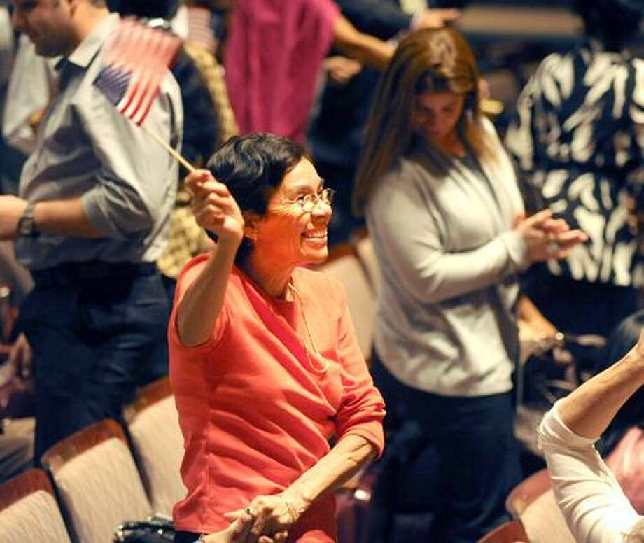Maria Reyes, of Lakeview, originally from Honduras, waves the American flag after taking the nation's oath of allegiance Tuesday, Sept. 21, 2010 during the annual naturalization ceremony for new American citizens at the Regina A. Quick Center for the Arts at Fairfield University in Fairfield, Conn. (AP Photo/The Connecticut Post, Autumn Driscoll) Photo: AP / Connecticut Post