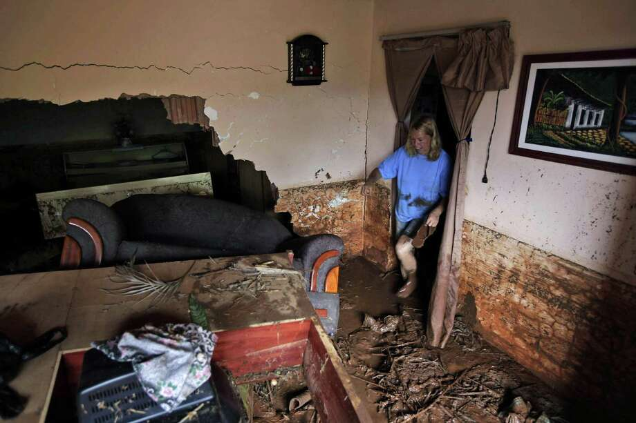 A woman tries to recover belongings from her damaged house after a landslide in Nova Friburgo, Brazil, Monday. Brazil's army on Monday sent 700 soldiers to help throw a lifeline to desperate neighborhoods that have been cut off from food, water or help in recovering bodies since mudslides killed at least 642 people. (AP Photo/Felipe Dana) Photo: ASSOCIATED PRESS / AP2011