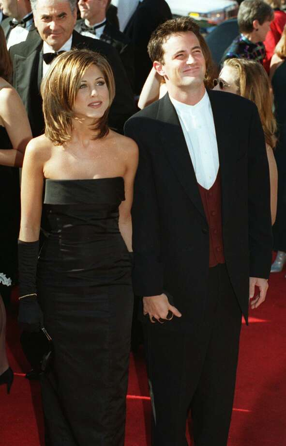 """A Sept. 10, 1995 file photo shows Jennifer Aniston and Matthew Perry, co-stars in the comedy series """"Friends,"""" arriving at the 47th Annual Primetime Emmy Awards ceremony in Pasadena, Calif.   Commenting on the hairstyle she wore in the first years of the series Anniston said """"I think it was the ugliest haircut I've ever seen."""" (AP Photo/Chris Pizzello/file) Photo: ASSOCIATED PRESS / AP1995"""