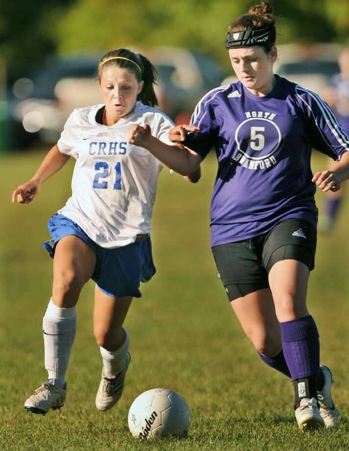 Coginchaug's Victoria Buonanni holds off a challenge by North Branford's Alex Stowe during a 3-0 Blue Devils win. (Catherine Avalone / TheMiddletownPress