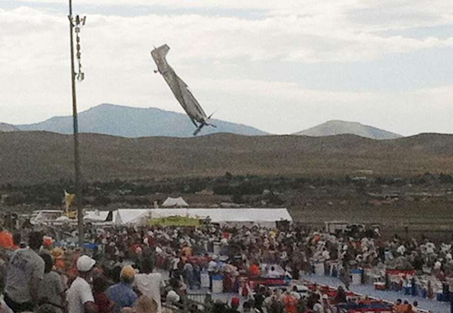 In this Friday photo, a P-51 Mustang airplane approaches the ground right before crashing during an air show in Reno, Nev. The vintage World War II-era fighter plane piloted by Jimmy Leeward plunged into the grandstands during the popular annual air show. (AP Photo/Garret Woodson) Photo: AP / 2011 AP
