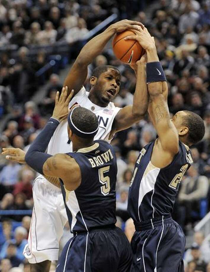 Connecticut's Jerome Dyson gets fouled while being guarded by Pittsburgh's Gilbert Brown and Jermaine Dixon during the first half of Wednesday's loss. (Associated Press) Photo: AP / FR153656 AP