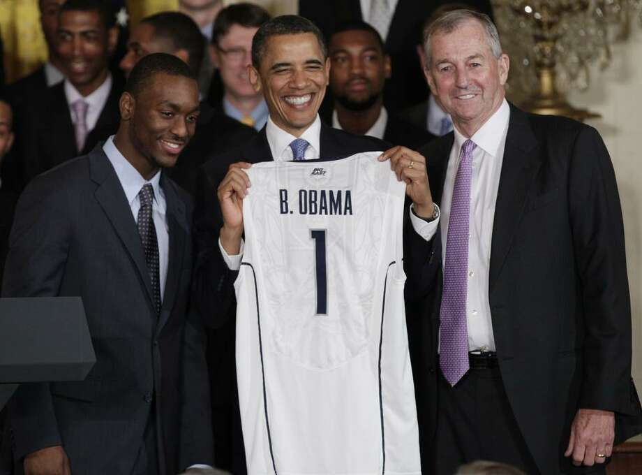 President Barack Obama, center, smiles with a jersey given to him by guard Kemba Walker, left, and coach Jim Calhoun as Obama greeted the Connecticut men's basketball team in the East Room of the White House, Monday, May 16, 2011, in Washington.  (AP Photo/Carolyn Kaster) Photo: ASSOCIATED PRESS / AP2011