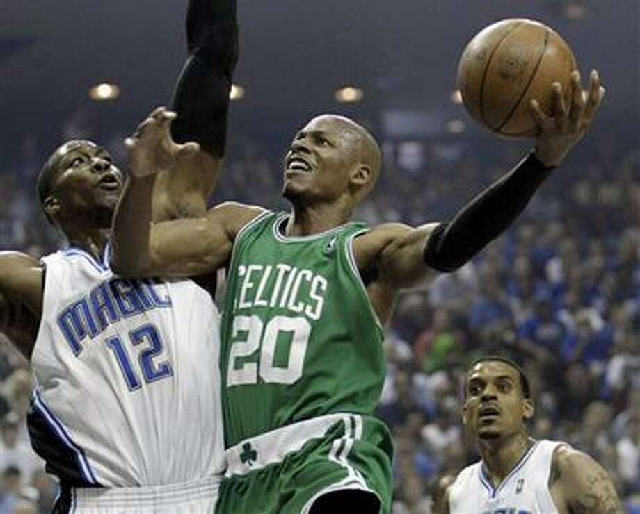 (AP) Boston Celtics guard Ray Allen (20) shoots over Orlando Magic center Dwight Howard (12) during the first half in Game 1 of the NBA Eastern Conference basketball finals in Orlando, Fla., Sunday. Photo: AP / AP