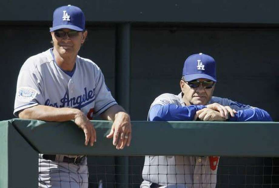 FILE - In this March 15, 2010, file photo, Los Angeles Dodgers' manager Joe Torre, right, and hitting coach Don Mattingly watch from the dugout rail as the Dodgers play the Los Angeles Angels in the third inning of a spring training baseball game in Tempe, Ariz.  A Dodgers official speaking on condition of anonymity tell The Associated Press that Joe Torre intends to retire as Los Angeles Dodgers manager at the end of the season and will be replaced by hitting coach Don Mattingly. (AP Photo/Jeff Chiu, File) Photo: ASSOCIATED PRESS / AP