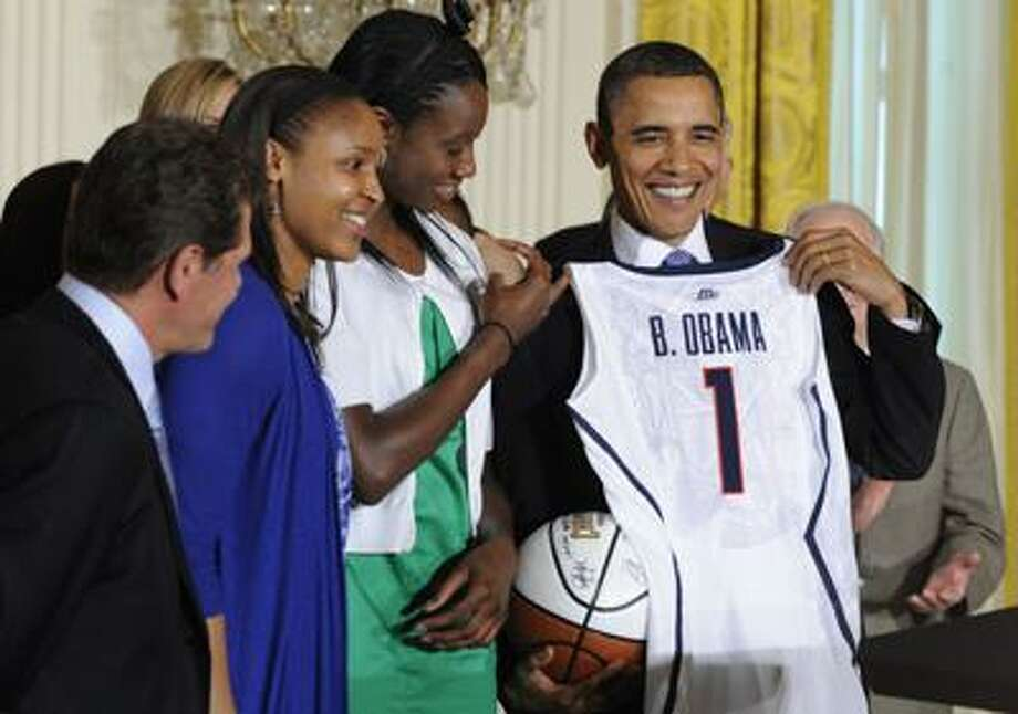 President Barack Obama holds a jersey and basketball that was presented to him by NCAA champion University of Connecticut women's basketball players Tina Charles, in green, and Maya Moore, blue, during a ceremony in the East Room of the White House in Washington, Monday. UConn coach Geno Auriemma watches at left. (AP) Photo: AP / AP