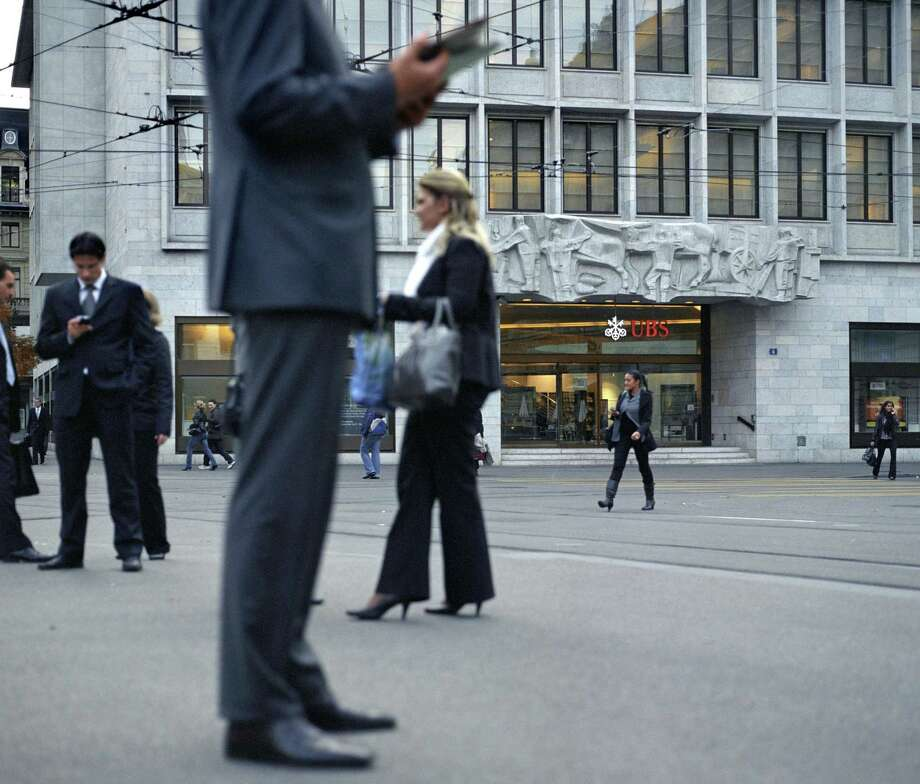 This photo shows business men standing in front of the UBS bank on Paradeplatz place in Zurich, Switzerland. Swiss bank UBS AG is revising its dress code after getting roundly mocked for suggesting employees wear skin-colored underwear and avoid garlic breath. The bank said Monday, it is whittling down its 44-page style guide to a more modest booklet that will concentrate on how to impress customers with a polished presence and sense of Swiss precision and decorum.(AP Photo/Keystone, Gaetan Bally) Photo: ASSOCIATED PRESS / AP2008