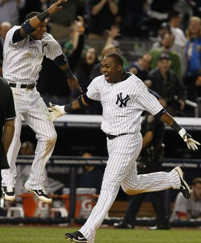 New York Yankees' Robinson Cano, left, leaps after Marcus Thames, right, hit a walkoff home run in the Yankees' 11-9 defeat of the Boston Red Sox in a baseball game at Yankee Stadium in New York, Monday. (AP) Photo: AP / AP