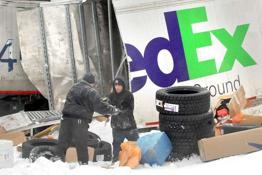 Workers unload parcels spilled  when a double trailer Fed Ex truck was cut in half at the train crossing in Wallingford at Rt 5 and Tolles Rd. VM Williams 01.18.11
