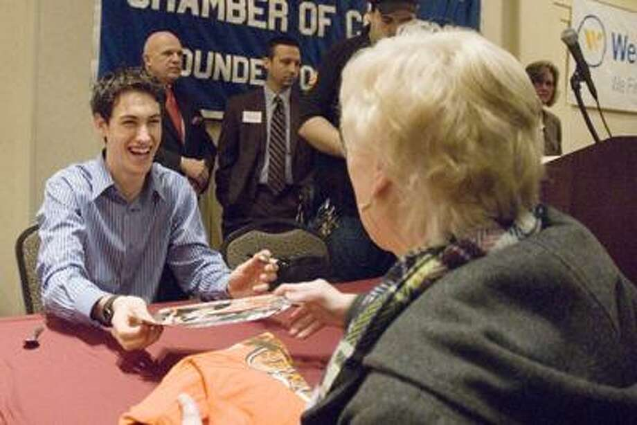 NASCAR driver and Middletown native Joey Logano autographs a photo for a woman Monday morning at the Chamber of Commerce breakfast at the Crowne Plaza Hotel in Cromwell. (Max Steinmetz / Special to the Press)