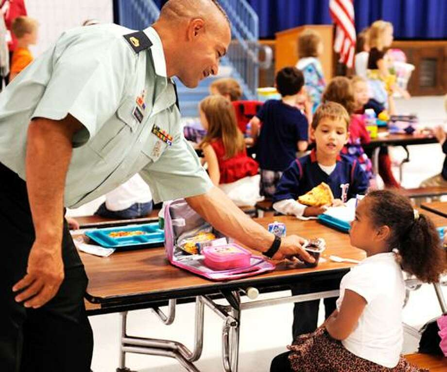 "Connecticut Army National Guard Staff Sergeant Turhan ""Pop"" Papadopoulos, of Norwich, hands kindergartener Chanel Holland her pudding, which he had just opened for her, as the greets students during lunch at North Stonington Elementary School  on  Friday, Sept. 17, 2010. Papadopoulos is half-way through a two-week leave home from Afghanistan and wanted to visit the school to personally thank students there for letters and cards they sent to him and his unit this summer.  (AP Photo/The Day, Sean D. Elliot) Photo: AP / 2010 The Day Publishing Company"
