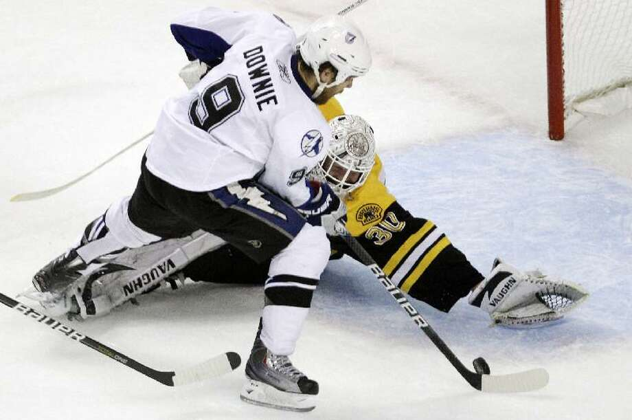 ASSOCIATED PRESS Boston Bruins goalie Tim Thomas dives to make a save against Tampa Bay Lightning right wing Steve Downie (9) during the second period of Game 1 of the Stanley Cup Eastern Conference final playoff series in Boston Saturday.