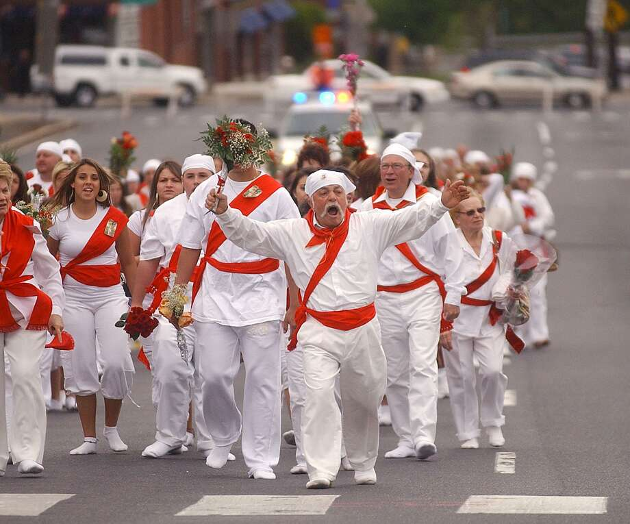 Dominic Guiliano leads a group of I Nuri runners clad in all white and red up Washington Street in Middletown Sunday for the St. Sebastian Feast. (Brenda De Los Santos