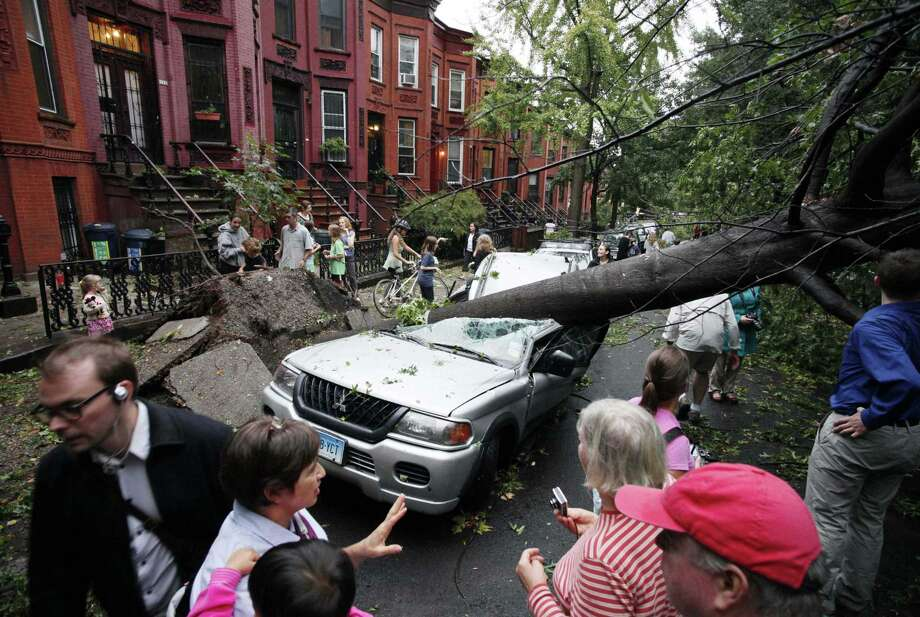 Residents in the Park Slope neighborhood in the Brooklyn borough of New York circle around a car crushed by a fallen tree, Thursday. A brief but severe storm has swept through New York City, uprooting trees and damaging cars. (AP Photo/Mark Lennihan) Photo: ASSOCIATED PRESS / AP