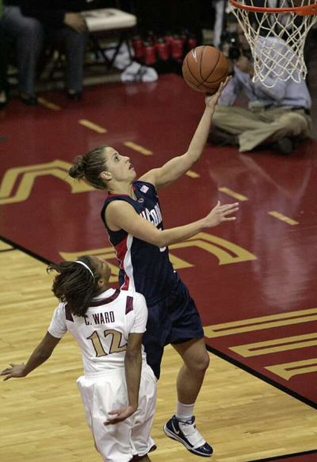 Connecticut's Caroline Doty drives the lane and scores past the defense of Florida State's Courtney Ward in the first half of a Dec. 28 game. (Associated Press) Photo: AP / FR127919 AP