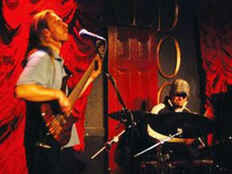 Two members of Closed Till Dark are shown performing on stage. (Courtesy photo)