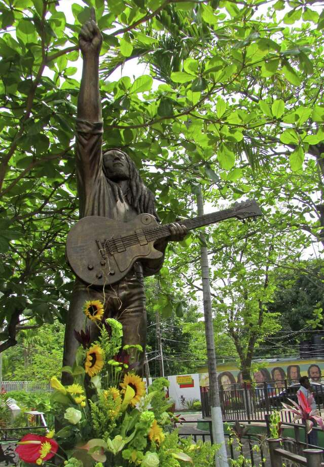The statue of reggae legend Bob Marley is seen adorned with a flower bouquet at his museum in Kingston, Jamaica, Wednesday. Reggae fans visited the Bob Marley museum in the Jamaican capital to mark the 30th anniversary of his death. (AP Photo/David McFadden) Photo: AP / AP
