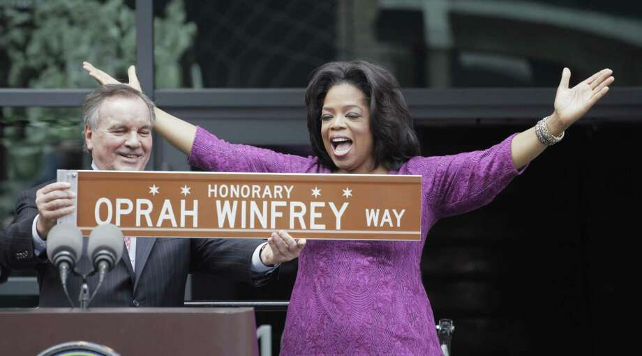 In one of his last acts before leaving office next week, Chicago Mayor Richard M. Daley presents TV talk-show host Oprah Winfrey with a sign after a street was named in her honor outside her Harpo Studios in Chicago, Wednesday. Winfrey will end her 25 year-run on daytime television in Chicago on May 25. (AP Photo/M. Spencer Green) Photo: ASSOCIATED PRESS / AP2011