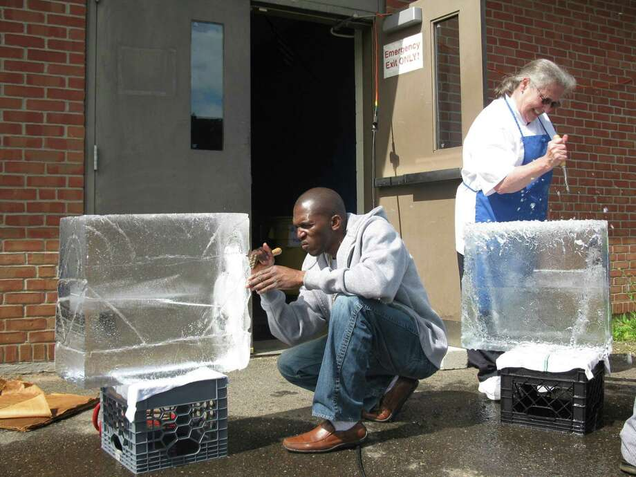 Leroy Grey (left) of the Crowne Plaza Cromwell Hotel and Mary Brewster (right) of the Captain Stannard House begin work on their ice sculptures outside of Vinal Technical High School on Wednesday in Middletown. The two students are part of a class of nine that will graduate on May 17.