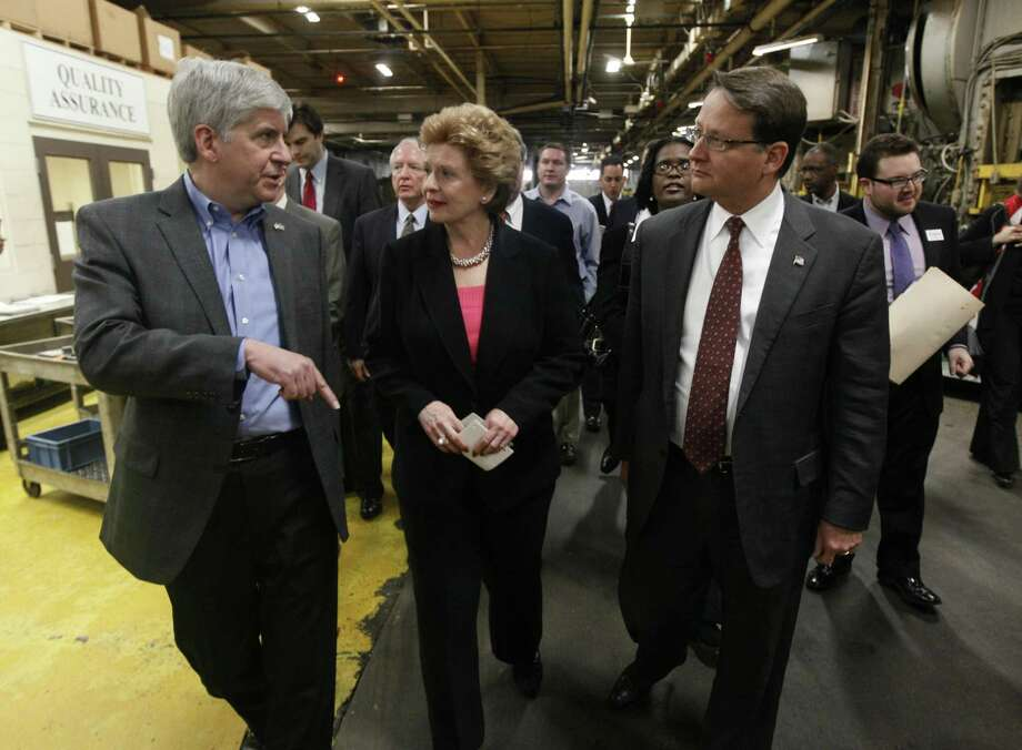 Michigan Gov. Rick Snyder, from left, talks with Sen. Debbie Stabenow, D-Mich., and Rep. Gary Peters, D-Mich., walking through United Metal Products to announce a new federal loan program aimed at helping small businesses at a news conference in Detroit, Friday.(AP Photo/Paul Sancya) Photo: AP / AP