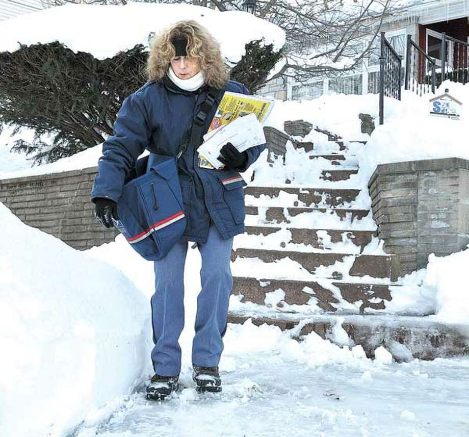 Letter Carrier Martha Phelan slowly navigates down an icy driveway as she delivered mail along Whittier Road in New Haven. She has been a carrier for 28-years, and this is one of the worst storms she can remember. (Photo by Peter Casolino/New Haven Register)