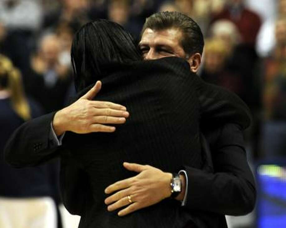 Connecticut head women's basketball coach Geno Auriemma (facing camera) gets a hug from former UConn player Jamelle Elliott before the start of the first half of Thursday's game. (Associated Press) Photo: AP / FR170410 AP