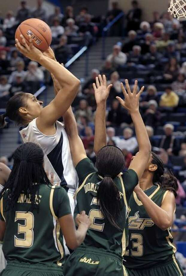 Connecticut's Maya Moore, top, goes up for a basket while guarded by South Florida's Kaneisha Saunders (3), Leondra Doomes-Stephens (2), and Jessica Lawson, right, in the first half of Monday's game. (Associated Press) Photo: AP / FR125654 AP