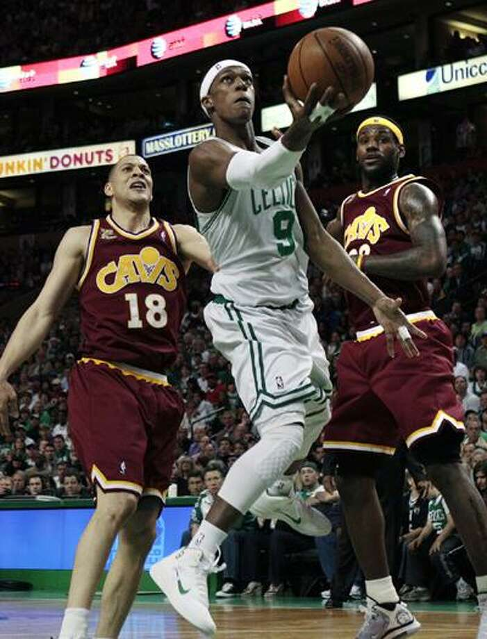 Boston Celtics guard Rajon Rondo (9) drives past Cleveland Cavaliers' Anthony Parker (18) and LeBron James, right, in the second half of Game 4 Sunday. (Associated Press) Photo: AP / AP