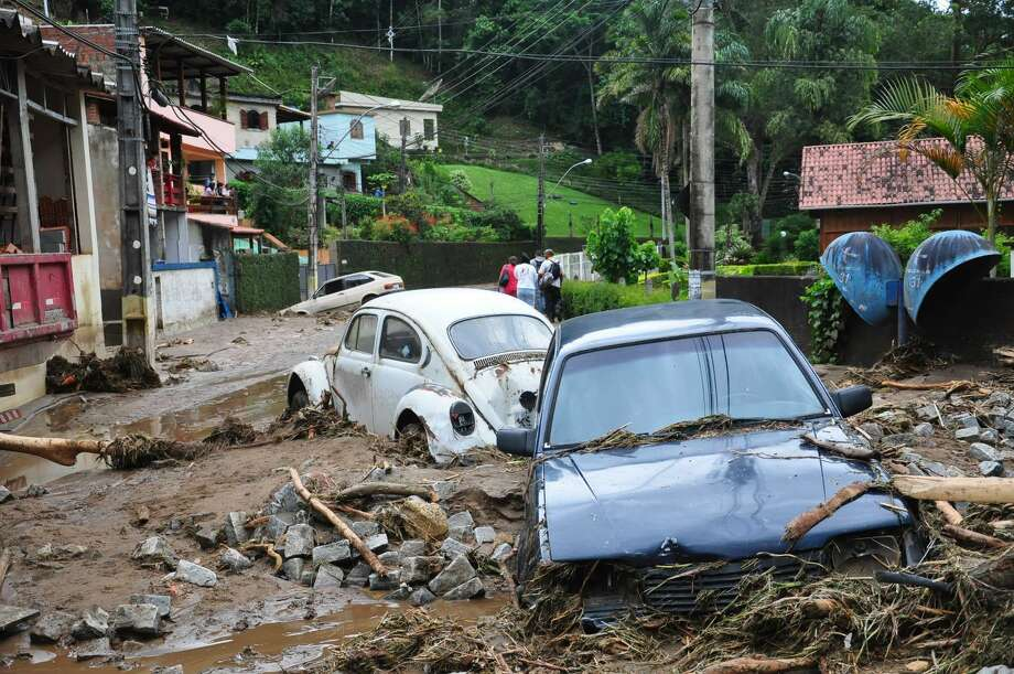 Cars sit in debris in a flooded street in Teresopolis, Rio de Janeiro state, Brazil, Wednesday. Torrential summer rains tore through Rio de Janeiro state's mountains, killing at least 140 people in 24 hours, Brazilian officials said Wednesday.  (AP Photo/Roberto Ferreira, Agencia O Dia) Photo: ASSOCIATED PRESS / AP2011
