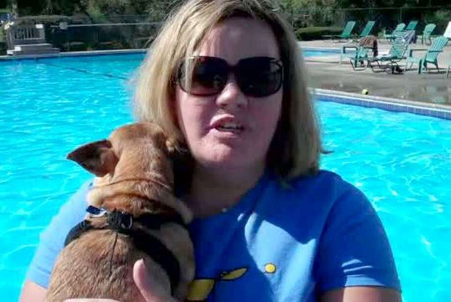 """Photo by Jeff MillAmanda Thomas, chairwoman of the Cromwell Dog Park Committee, discusses the first-ever """"doggy plunge"""" fundraiser held Sarruday at the Cromwell Hills condominium complex."""
