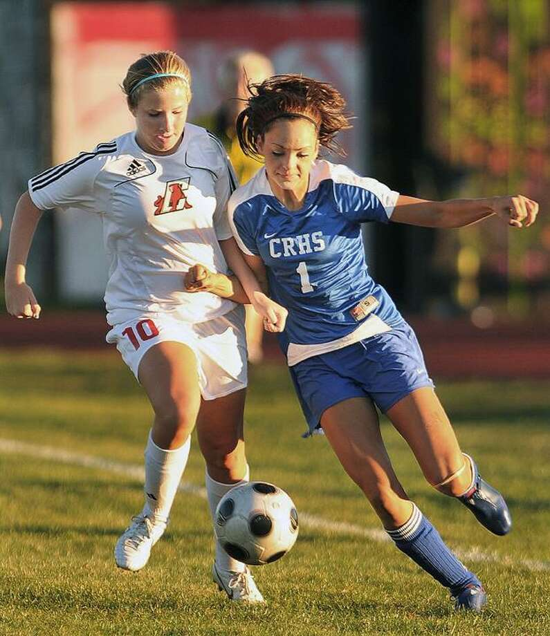 "Coginchaug junior Lauren Esposito battles Cromwell junior Bernie McMahon for possession during a season-opener in Cromwell. To buy a glossy print of this photo and more, visit <a href=""http://www.middletownpress.com"">www.middletownpress.com</a>. (Catherine Avalone / TheMiddletownPress"