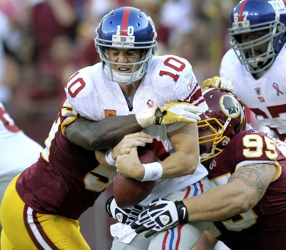 New York Giants quarterback Eli Manning is sacked by Washington Redskins linebacker London Fletcher, left, and nose tackle Chris Neild, right, during the second half of an NFL football game on Sunday, Sept. 11, 2011, in Landover, Md.  (AP Photo/Susan Walsh) Photo: ASSOCIATED PRESS / AP2011