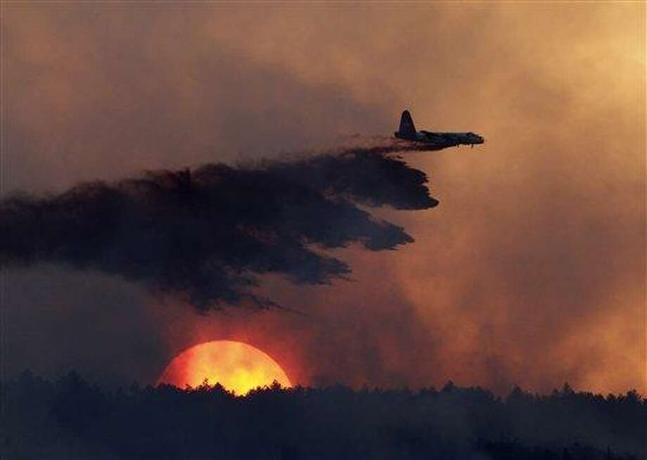 A slurry bomber drops retardant on a burning ridge as the sun sets behind it as a wildfire burns west of Loveland, Colo., on Sunday, Sept. 12, 2010. (AP Photo/Ed Andrieski) Photo: AP / AP