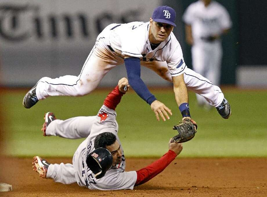 ASSOCIATED PRESS Boston Red Sox first baseman Adrian Gonzalez, bottom, slides into second base in an attempt to break up a double-play throw by Tampa Bay Rays shortstop Sean Rodriguez, top, to put out batter David Ortiz during the ninth inning of Saturday's game in St. Petersburg, Fla. The Rays won 6-5 in 11 innings.